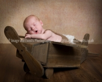 Newborn baby boy in wooden toy aeroplane
