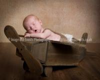 Newborn baby boy in wooden toy aeroplane