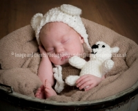 Newborn baby boy fast asleep in bucket